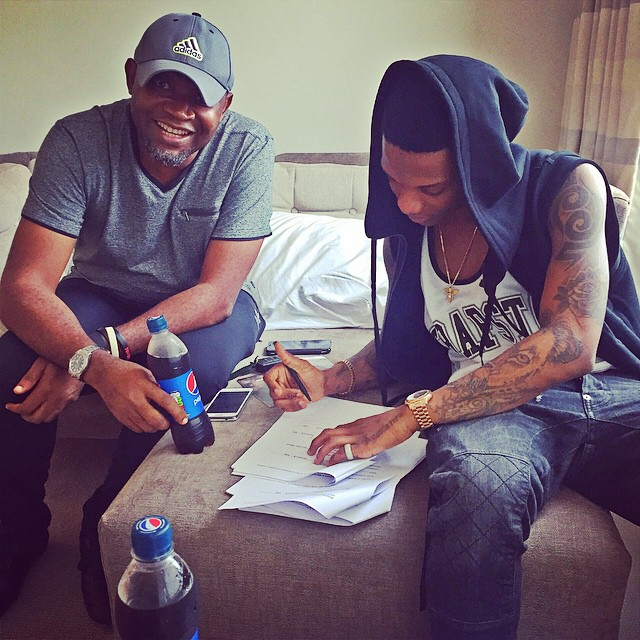 Paul O and Wizkid signing a Pepsi endorsement